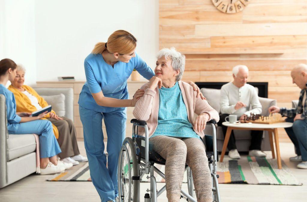 Elder woman accompanied by nurse in senior home community.