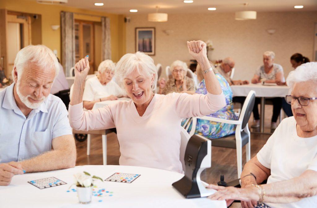Seniors sitting at table in dinning room playing bingo
